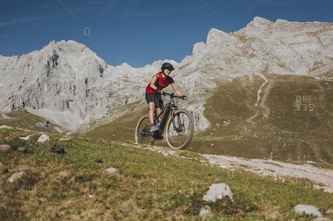 Female cyclist riding mountain bike on trail at Picos de Europa National Park- Cantabria- Spain