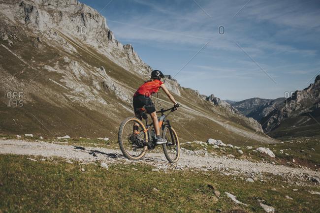 Female cyclist riding mountain bike at Picos de Europa National Park- Cantabria- Spain