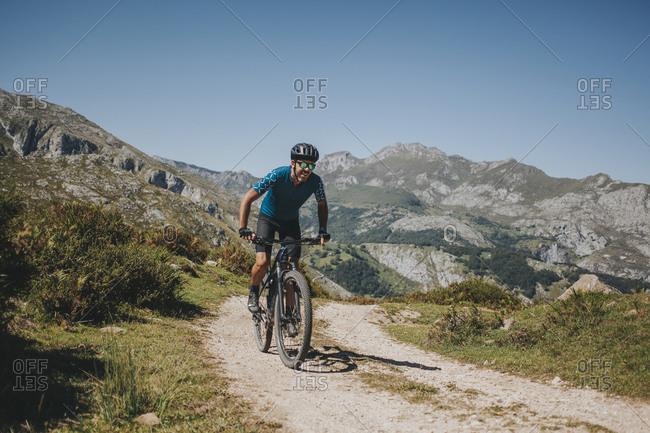 Male cyclist riding mountain bike on trail against sky- Picos de Europa National Park- Asturias- Spain