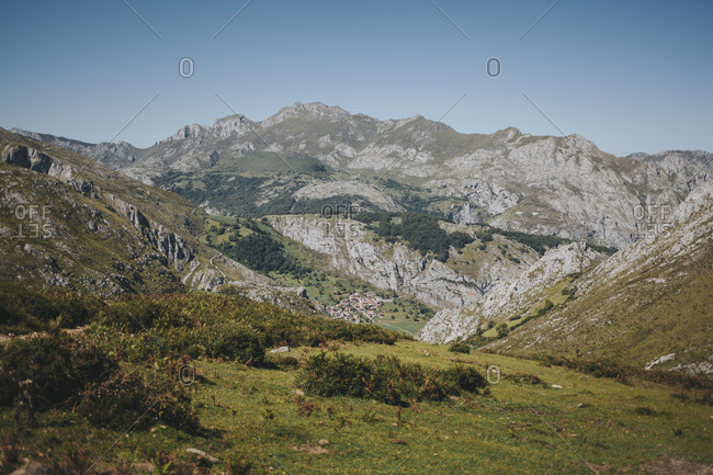 Distant view of Bejes village against mountain range on sunny day- Picos de Europa National Park- Asturias- Spain