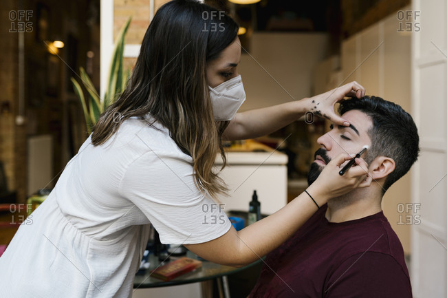 Young female stylist applying make-up to groom in salon during coronavirus