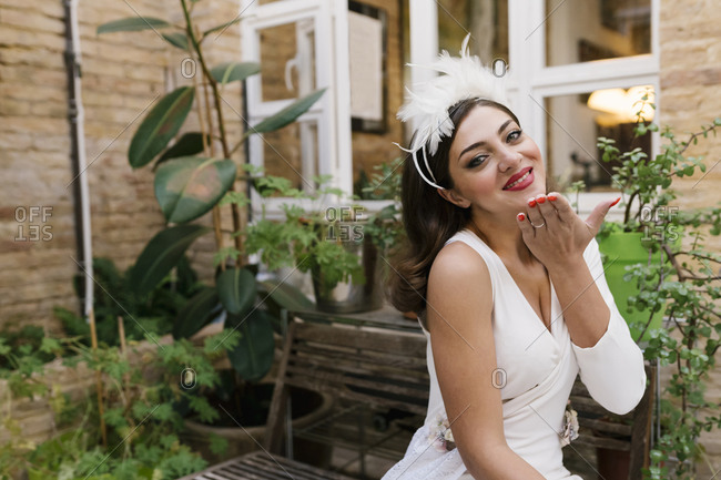Smiling bride giving flying kiss while sitting in garden against plants