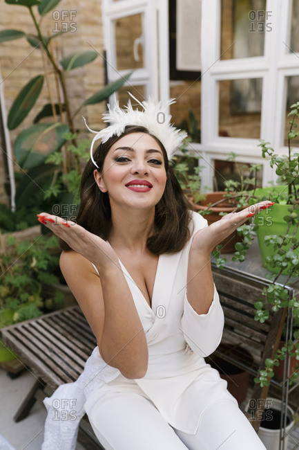 Happy young bride giving flying kiss in garden against plants