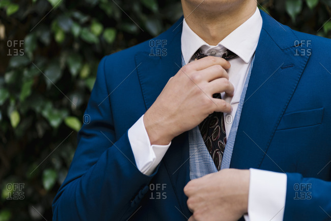 Young bridegroom adjusting necktie at park