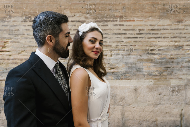 Happy married couple standing by wall