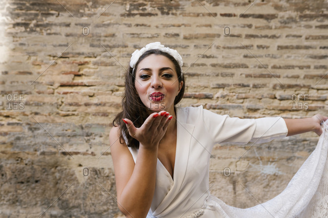 Young bride flying kiss while holding wedding dress against wall