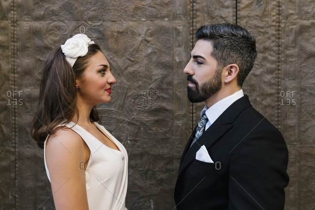 Smiling couple standing face to face by door of church