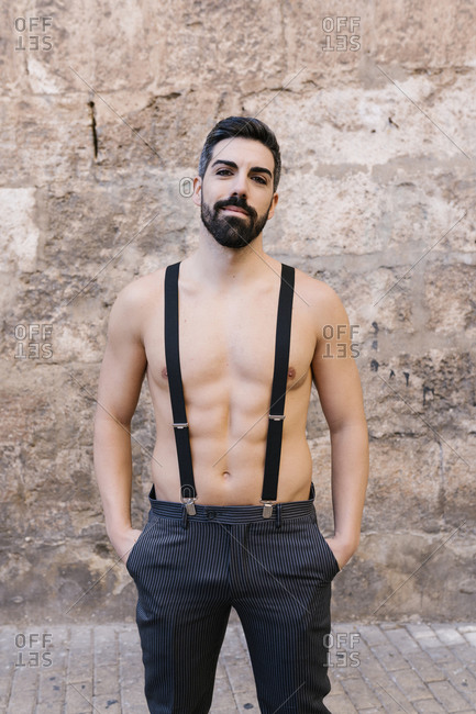 Groom standing shirtless with suspenders against wall