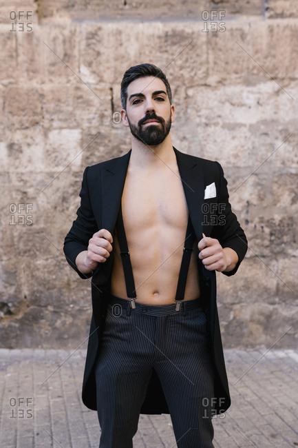 Elegant shirtless groom wearing suspenders against wall