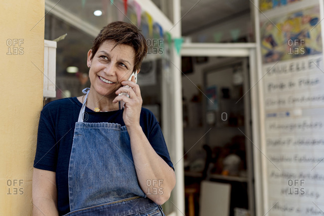 Mature store owner talking on mobile phone standing by door of workshop