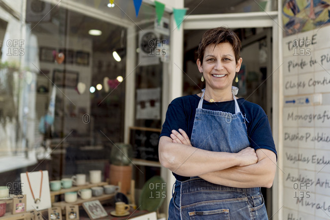 Happy small business owner standing with arms crossed outside her store