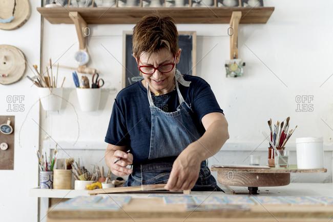 Mature female craftsperson working in ceramics store