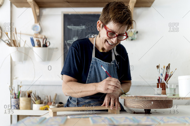 Smiling owner painting craft product in ceramic workshop