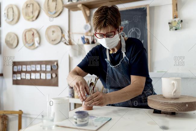 Female artist working in ceramic workshop during COVID-19