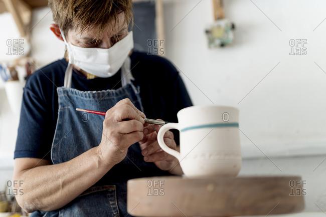 Female artist painting cup in ceramic workshop