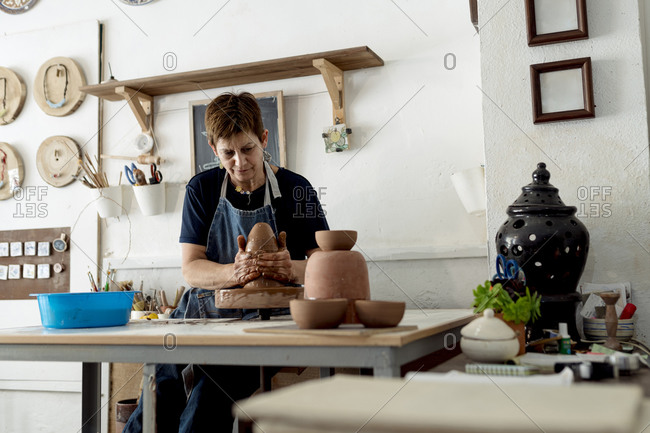 Mature female artist making pottery from brown clay in ceramic store