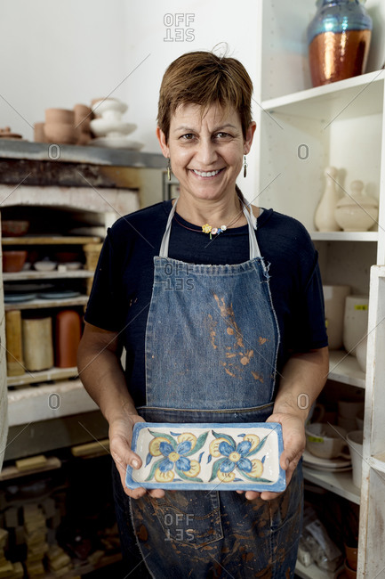 Happy female artist showing her designs at ceramic workshop