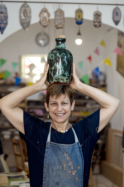 Smiling artist carrying turquoise bottle on head at ceramic store