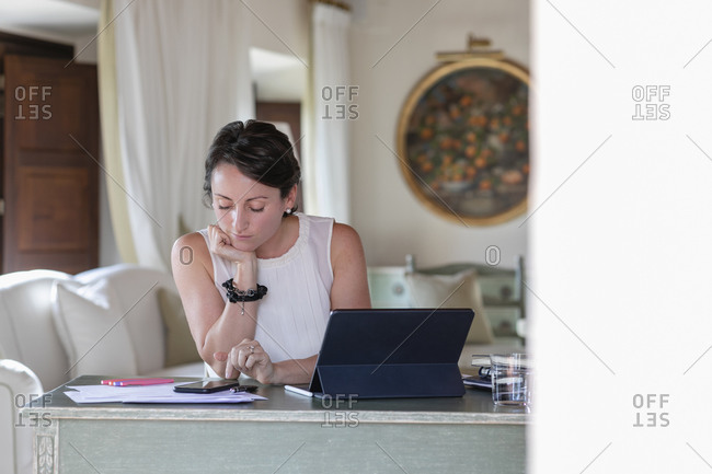 Businesswoman with hand on chin using smart while working at home