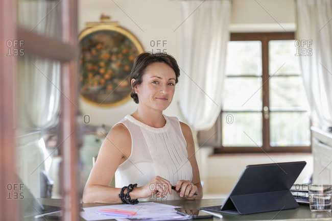 Creative female professional sitting by digital tablet in home office