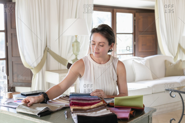 Female wedding planner choosing fabric swatches while working at home
