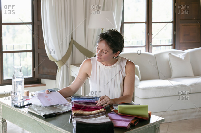 Creative female event planner choosing colors from fabric swatches while sitting at home