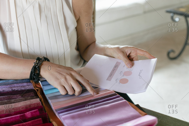 Female event planner choosing colors from fabric swatches at home