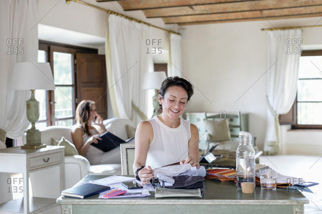 Smiling businesswoman choosing fabric while female colleague talking on smart phone at home office