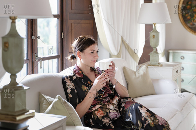 Businesswoman holding drinking glass while sitting on sofa at home