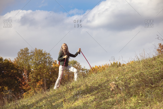 Mature woman with hiking pole hiking on mountain against sky at Alpine Foothills- Germany