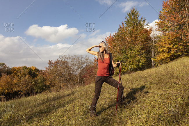 Woman with hiking pole looking away while standing on mountain at Alpine Foothills- Germany