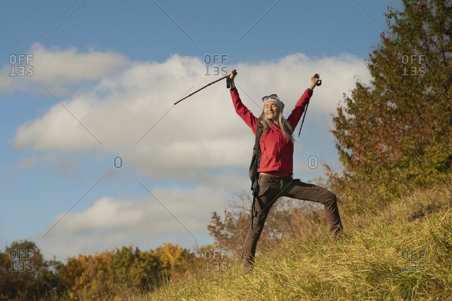 Smiling woman standing with hand raised on mountain against sky at Alpine Foothills- Germany