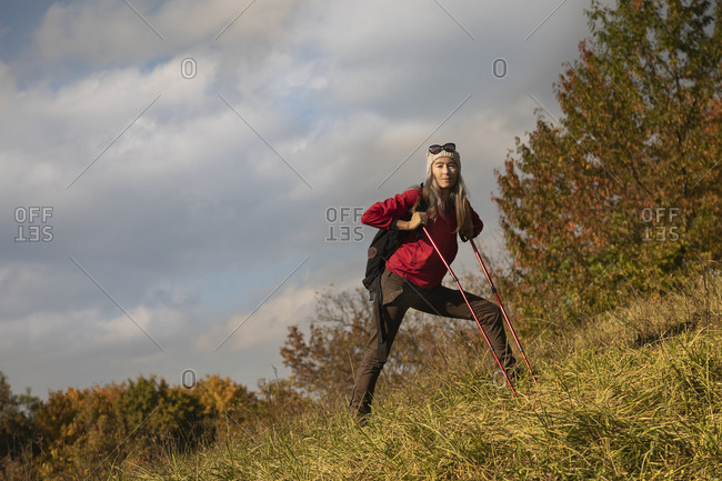 Mature woman with hiking pole and backpack walking on mountain at Alpine Foothills- Germany