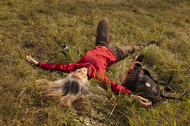 Carefree woman resting while lying on mountain at Alpine Foothills- Germany