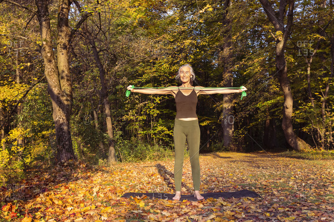 Mature woman exercising with resistance band at park during autumn