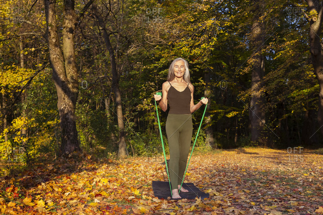 Smiling woman exercising with resistance band on mat at park during autumn