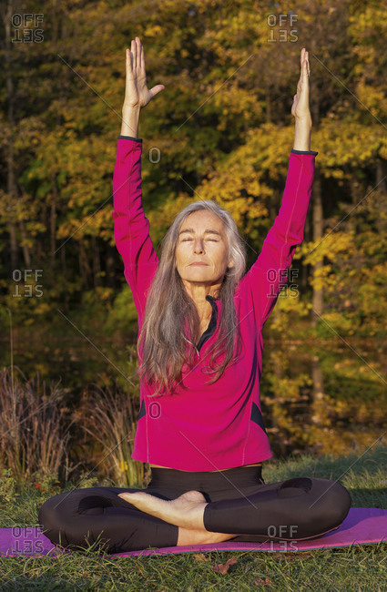 Active woman with eyes closed raising arms while practicing yoga at park during autumn