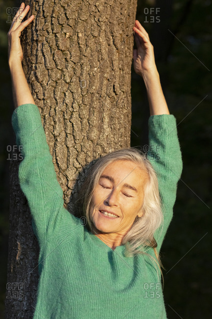 Mature woman with eyes closed against tree trunk at park during autumn