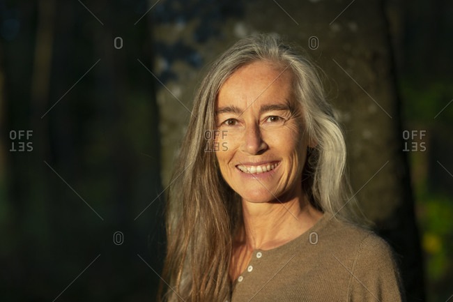 Smiling mature woman smiling against tree trunk in forest