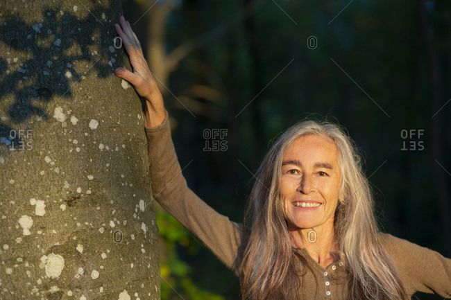 Smiling woman standing by tree trunk at park