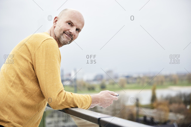 Smiling man using mobile phone while standing on rooftop
