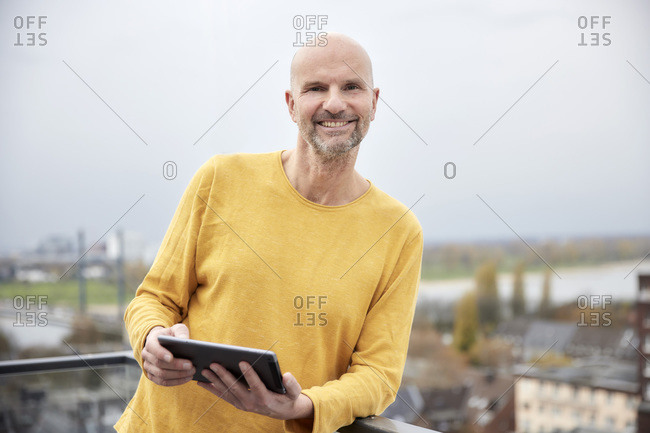 Man with digital tablet smiling while standing on rooftop