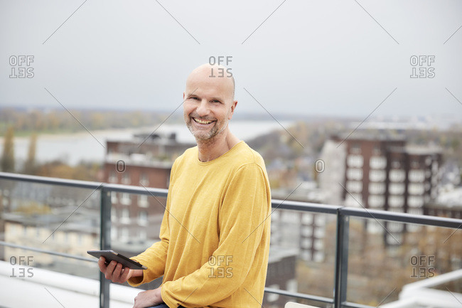 Smiling man using digital tablet while sitting on rooftop