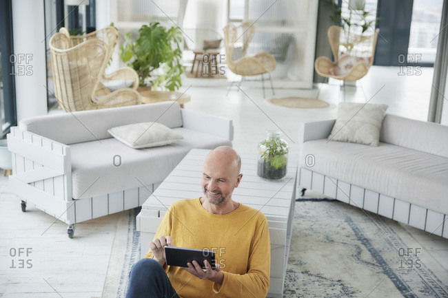 Mature man using digital tablet while sitting on floor at home