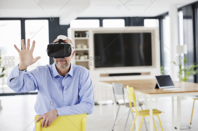 Businessman wearing virtual reality headset touching while sitting on chair