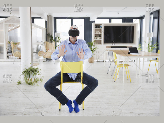 Mature businessman using virtual reality headset while sitting on chair at home office