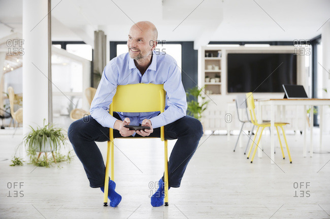 Businessman with digital tablet looking away while sitting on chair at home office