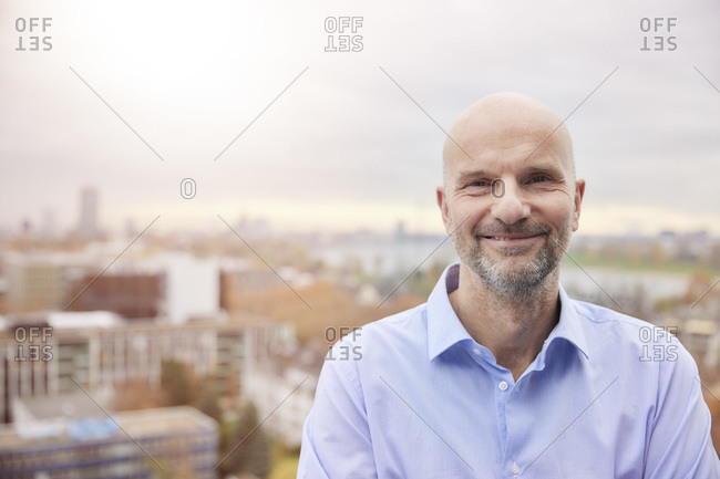 Mature businessman smiling while standing on rooftop