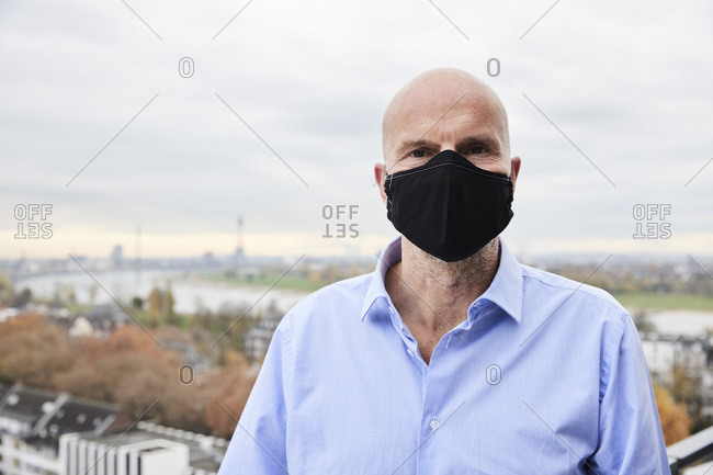 Mature businessman wearing protective face mask standing on rooftop