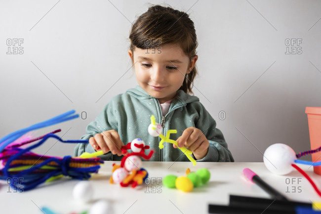 Smiling girl playing with pipe cleaners and pom-pom toys against wall